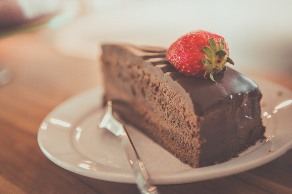 Chocolate cake with strawberry on a top on a dessert plate